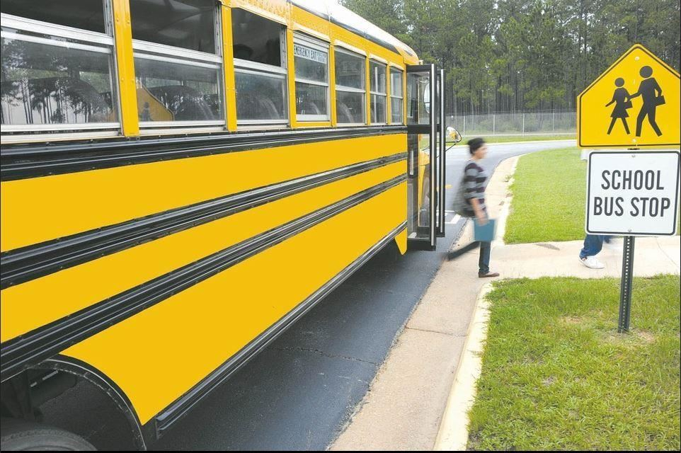 Child exiting a school bus at a bus stop.